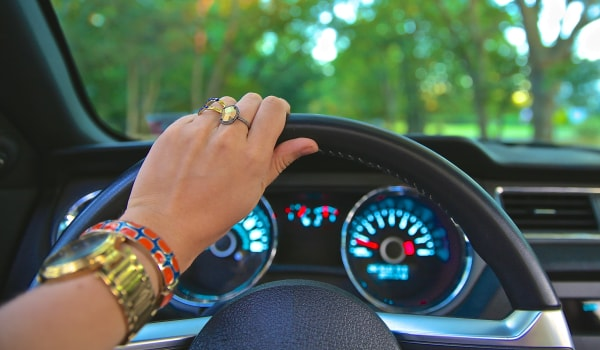 Hand with rings holding top of steering wheel
