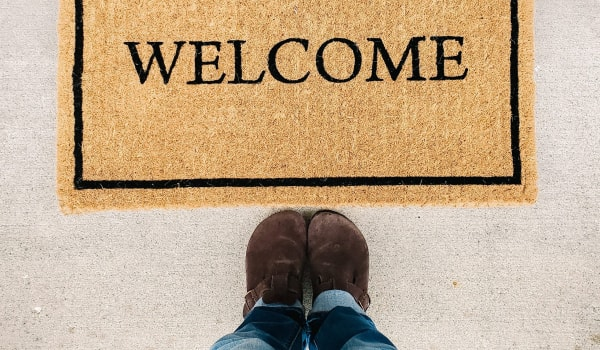 Welcome mat with lower body of person standing in front of it