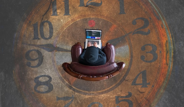 Person in chair on laptop with large clock in background