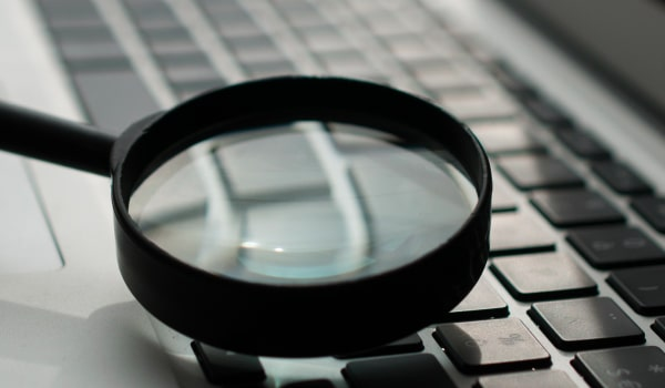 A magnifying glass over a laptop keyboard